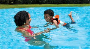 Mom teaching son to swim with flotation aid
